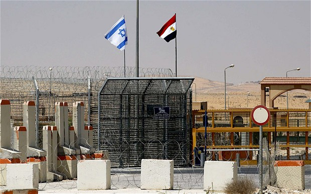 An Israeli flag flutters next to an Egyptian one at the Nitzana crossing as Israel has deployed hundreds of intelligence agents on its southern border with Egypt to combat the growing threat of attack from Jihadist groups in the neighbouring Sinai peninsula. , along Israel's border with Egypt's Sinai desert