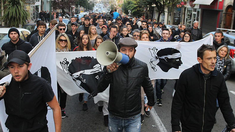 Angry protesters march with the Corsican flag