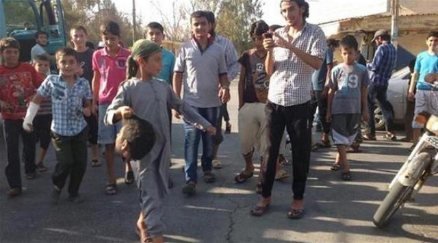 The young boy carrying the severed head in Syria seems to be about 12 years old