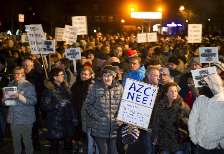 """A child can be seen holding a sign in Dutch. It reads in English: Asylum Center No! Council: You won't help us with our own housing…"""""""