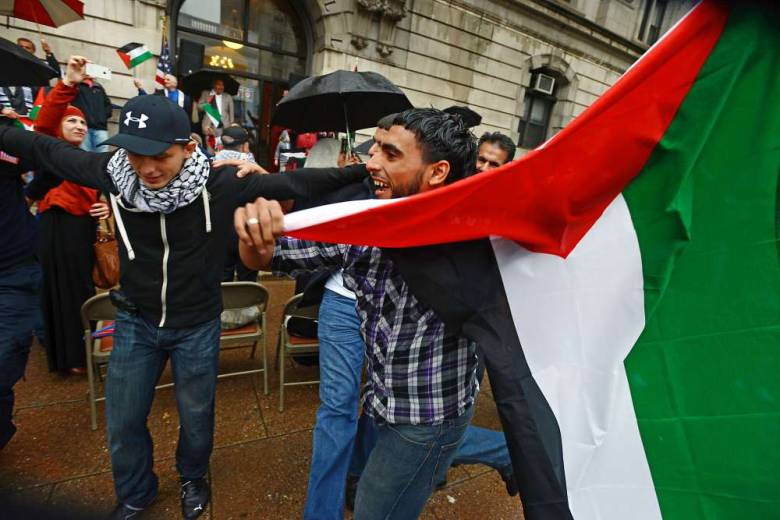 Abdel Rahman Ramadan of Paterson holding a Palestinian flag as he and others danced after a Palestinian flag was raised at Paterson City Hall. Mayor Jeffery Jones declared May 19 Palestinian-American Day in the city.