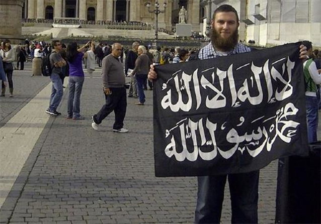Musa Cerantonio outside the Vatican with black flag of jiahd