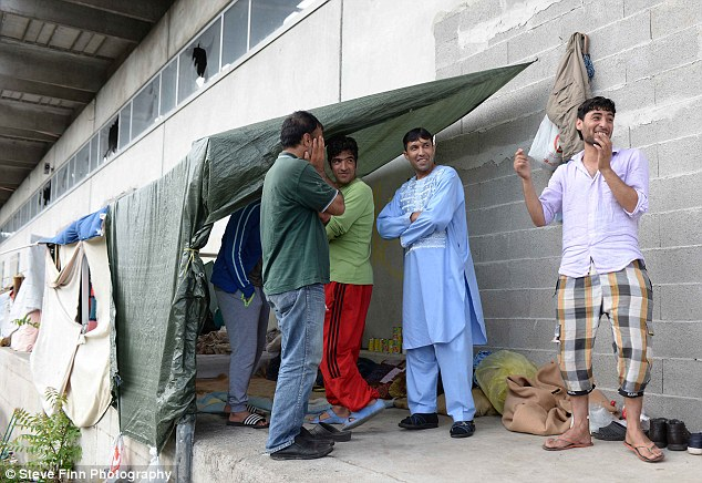 The new Lake Como residents have turned the town's railway station into a campsite. Pictured, Hamid (right) and his friends who are sleeping rough at the station