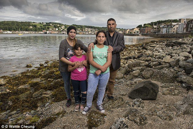 Feeling trapped: Hassan, 41, and his wife Fatima, 31, with their daughters, aged nine and 11, who are struggling to cope with life in Rothesay on the Isle of Bute