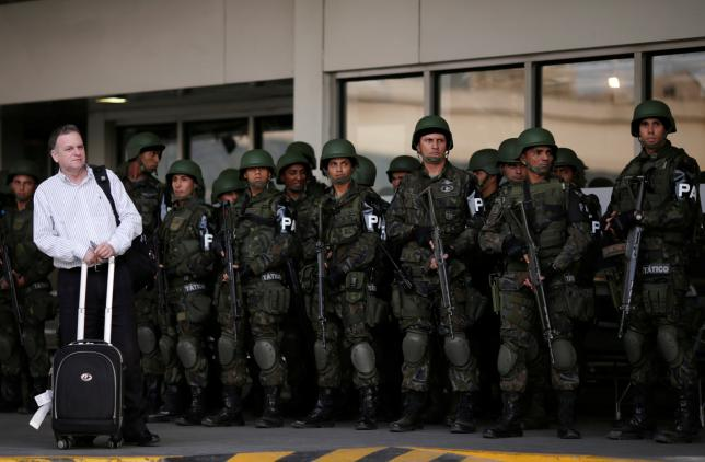 A passenger waits as Brazilian Air force soldiers patrol the Tom Jobim International airport ahead of the 2016 Rio Olympics in Rio de Janeiro