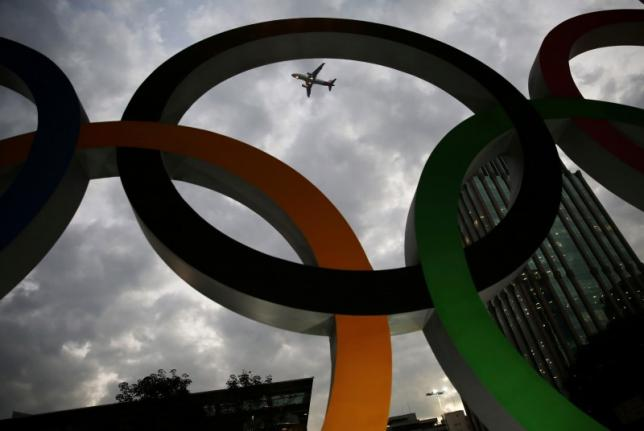 Airplane flies past Olympic rings placed at the entrance of office building ahead of the Rio 2016 Olympic Games