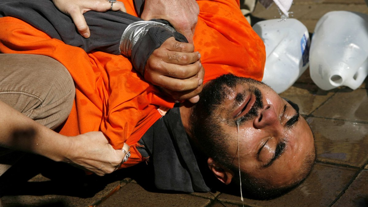 A demonstrator is helped up after his ordeal in a simulation of waterboarding in Washington