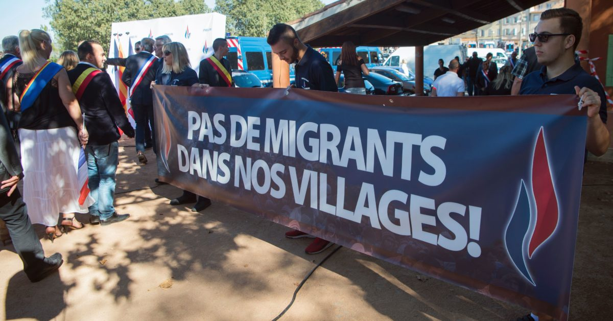 "Front National (FN)'s supporters hold a banner which translates as ""No migrants in our villages"" as they take part in a rally against the possibilty of welcoming refugees in a camp in Pierrefeu-du-Var"