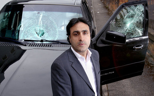 Hussein stands in front of his car that was vandalized by his Muslim neighbors